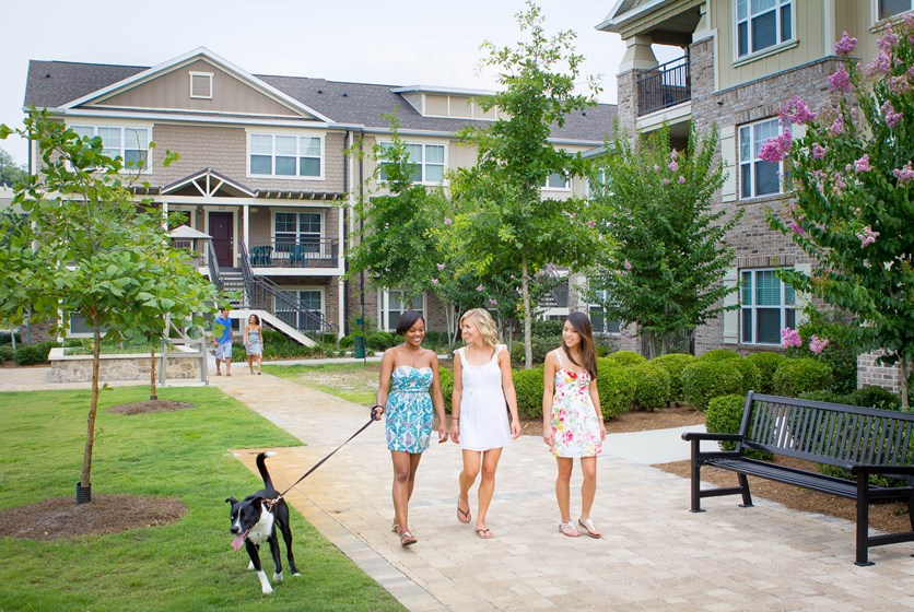 Girls walking with dogs in apartment community.
